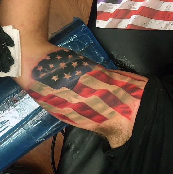 Realistic Flying US Flag Tattoo On Biceps