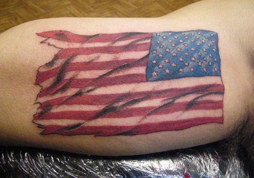 Torn American Flag Tattoo On Biceps