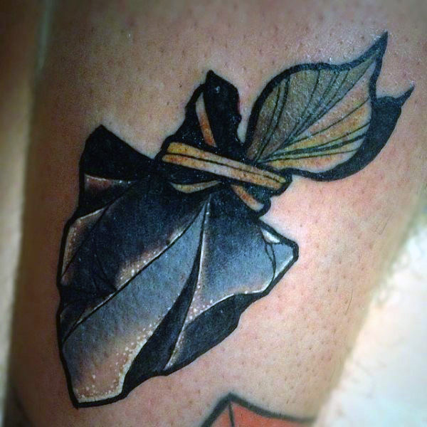 Guy With Pale Colored Arrowhead Tattoo On Legs