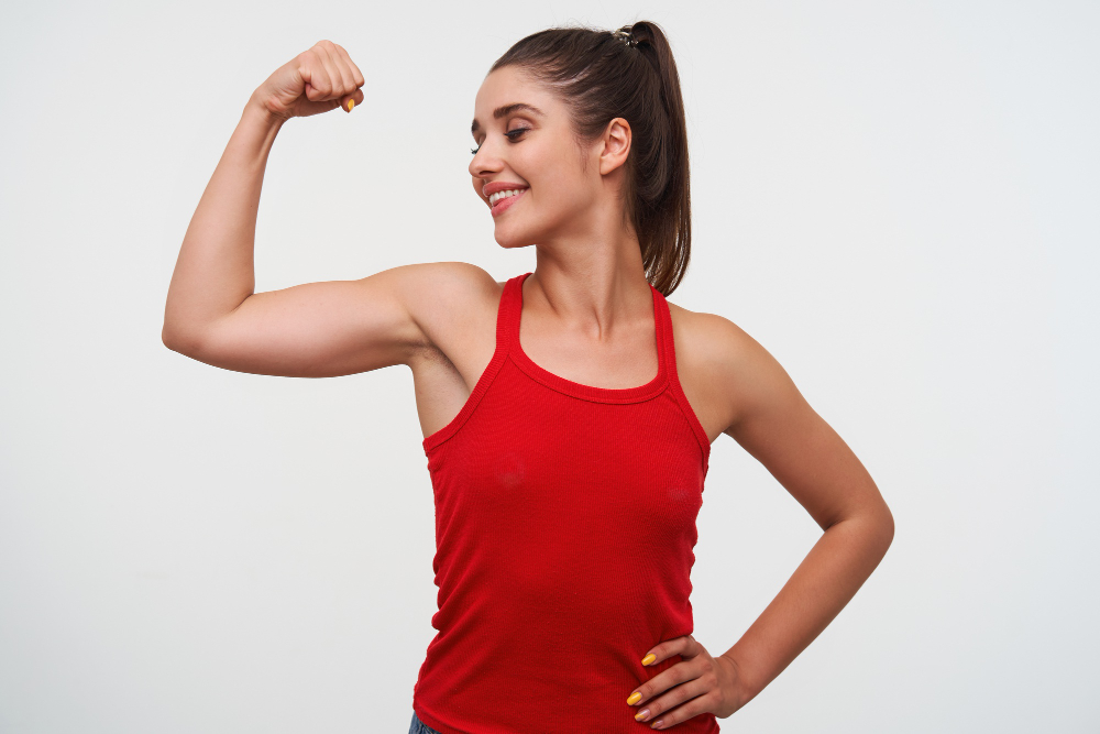 Portrait Young Smiling Cute Brunette Woman Wears Red T Shirt Demonstrates Beceps Excellent Fitness Form Stands White Background