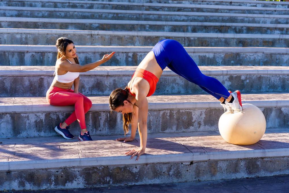 Young Caucasian Female Friends Doing Exercises Stretching Outside Healthy Lifestyle Concept